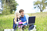 Father and daughter sitting on meadow, father working on laptop - MAEF011733