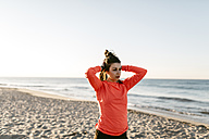 Woman running on the beach early in the morning, hands in hair - JRFF000667