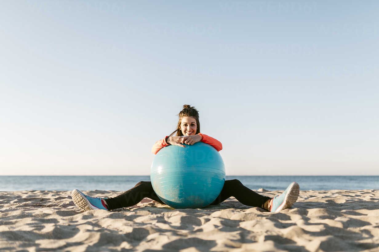 Woman doing sports with gym ball early in the morning on the beach - JRFF000670 - Josep Rovirosa/Westend61