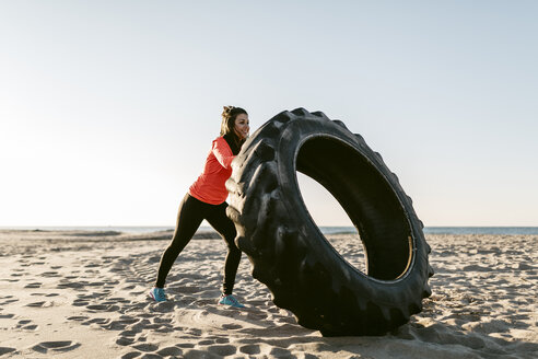 Woman doing sports with tractor tire early in the morning on the beach - JRFF000673