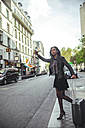 France, Paris, young woman hailing a taxi - ZEDF000124