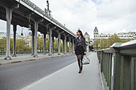France, Paris, young woman walking on bridge - ZEDF000127