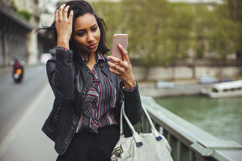 France, Paris, young woman looking at smartphone - ZEDF000130