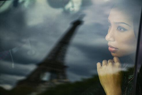 France, Paris, portrait of young woman watching Eiffel Tower through car window - ZEDF000133