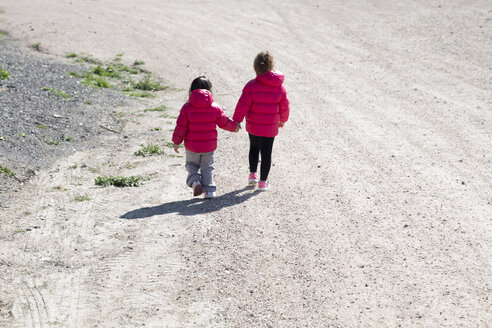 Back view of two little sisters walking hand in hand - ERLF000170
