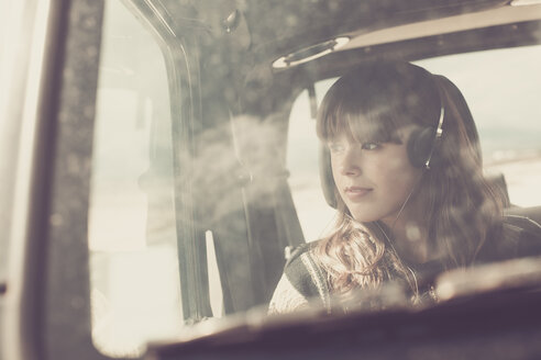 Young woman travelling in car listening music - SIPF000470