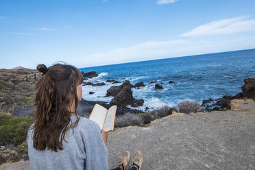 Young woman reading book at the sea - SIPF000476