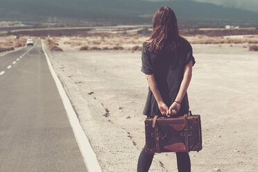 Young woman with suitcase walking on a road - SIPF000479