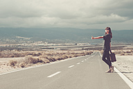 Young woman with suitcase hitchhiking on road - SIPF000482