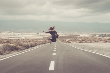 Young woman jumping for joy on a road - SIPF000485