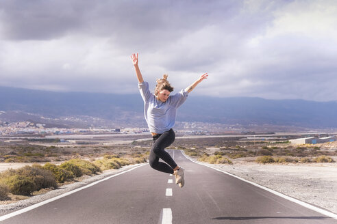 Young woman jumping for joy on a road - SIPF000491
