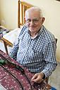 Portrait of smiling senior man with his model railway - RAEF001156