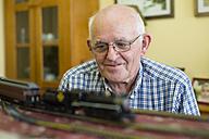 Portrait of smiling senior man with his model railway - RAEF001159
