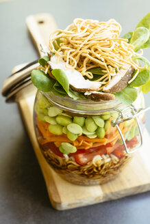 Asian salad in a jar with ramen noodles, red pepper, snow pea pods, carrots, edamame, shiitake mushrooms, salad greens, fried chow mien noodles and dressing - HAWF000897