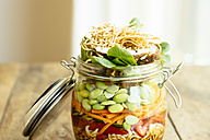 Asian salad in a jar with ramen noodles, red pepper, snow pea pods, carrots, edamame, shiitake mushrooms, salad greens, fried chow mien noodles and dressing - HAWF000900