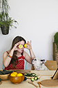 French bulldog watching woman covering her eyes with lemon halves - RTBF000203