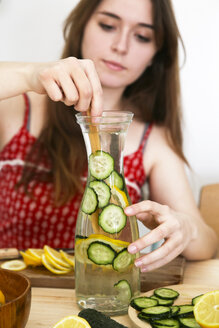 Woman preparing detox water infused with lemon and cucumber - RTBF000206