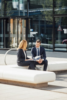 Businessman and businesswoman talking outside office building - CHAF001725