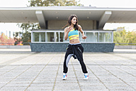 Young woman doing Tai Chi outdoors - ASCF000598