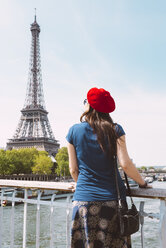 France, Paris, back view of woman wearing red beret looking at Eiffel Tower - GEMF000896