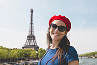 France, Paris, portrait of smiling woman wearing sunglasses and red beret in front of Eiffel Tower - GEMF000899