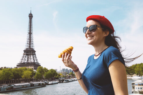France, Paris, woman with croissant standing in front of Seine river and Eiffel Tower - GEMF000902