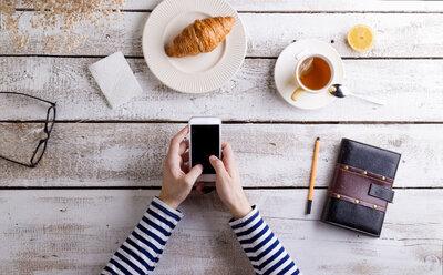 Man working smart phone and personal organiser while having breakfast - HAPF000355