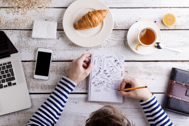 Man working at table with croissant and tea, taking notes - HAPF000358