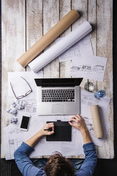 Architect working at desk with laptop, making sketches - HAPF000376