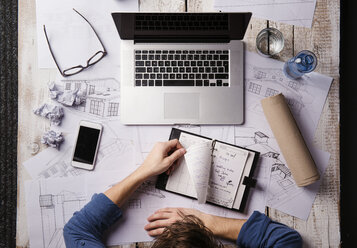 Architect working at desk with laptop, looking at peronal organiser - HAPF000379