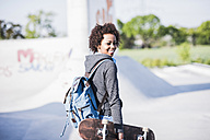 Smiling young woman with skateboard - UUF007237