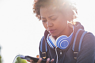 Young woman wearing headphones looking at cell phone outdoors - UUF007243