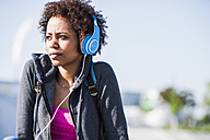 Young woman wearing headphones outdoors - UUF007249