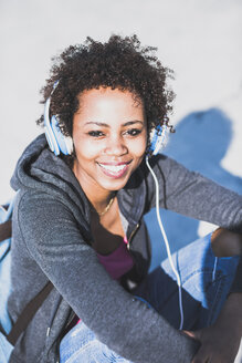 Portrait of smiling young woman wearing headphones outdoors - UUF007252