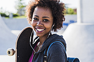 Portrait of smiling young woman with skateboard listening to music - UUF007261
