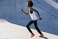 Young woman running in skatepark - UUF007273
