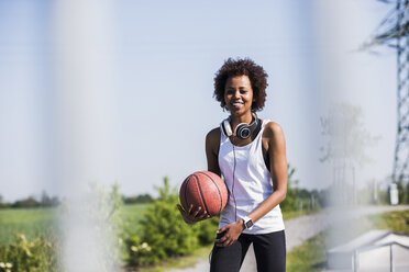 Smiling young woman holding basketball - UUF007285