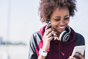 Smiling young woman wearing headphones looking at cell phone outdoors - UUF007303