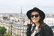 France, Paris, portrait of happy woman at viewpoint wearing a black hat and sunglasses - GEMF000906