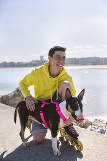 Portrait of smiling inline-skater with his bull terrier - MGOF001846