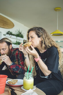 Couple having breakfast in cafe, eating sandwiches and organic juices - DAPF000096