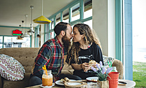 Couple kissing at breakfast in cafe - DAPF000099