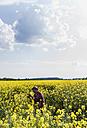 Farmer in field examining rape blossom - UUF007323