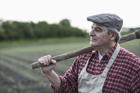 Farmer holding tool in front of a field - UUF007329