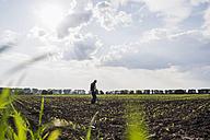 Farmer standing in a field - UUF007341
