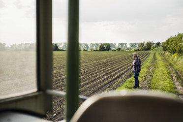 Farmer standing at a field - UUF007350