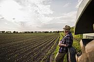 Farmer standing at a field - UUF007365