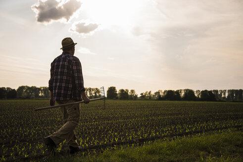 Farmer walking with rake along a field - UUF007368