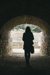 Spain, Merida, back view of woman in a tunnel - ABZF000521