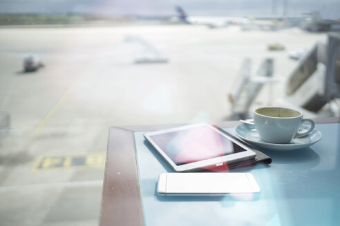 Coffee cup, smartphone and digital tablet on table at airport - RIBF000392